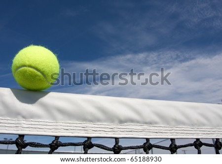Tennis Ball on the Court Net with room for copy - stock photo