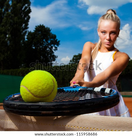 Tennis ball on the racket to the background of a beautiful woman. Close-up - stock photo