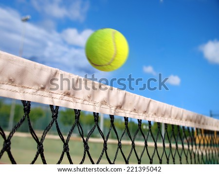 Tennis ball passing over the net      - stock photo