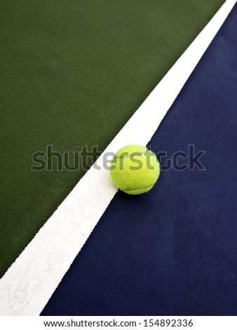 Tennis ball rests on the white line on the tennis court. - stock photo
