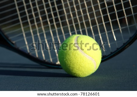 Tennis Ball with a racket in the background - stock photo
