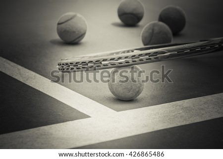 Tennis Ball with Racket on the clay tennis court, black and white - stock photo