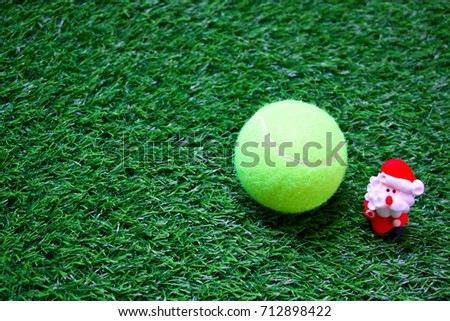 Tennis ball with Santa are on green grass