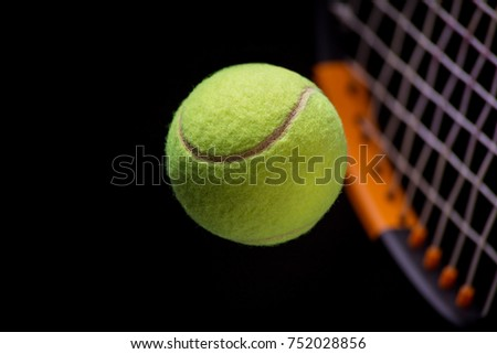 Tennis ball with tennis racquet in close black background.