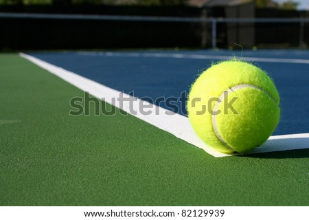 Tennis Ball with the court beyond - stock photo