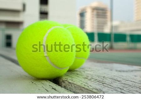 tennis balls and a hard court on a roof of high building - stock photo