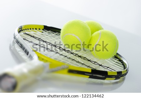 Tennis balls and racket against a white background - stock photo