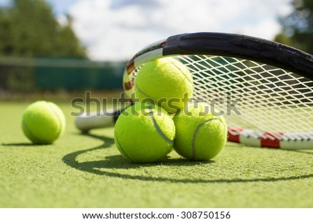 Tennis balls and racket on the grass court - stock photo