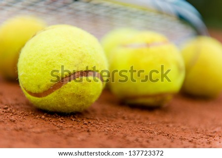 Tennis balls at the clay court with a racket - stock photo