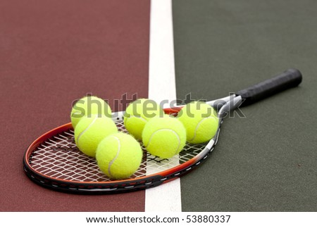 Tennis balls on a racket on the court ground - stock photo