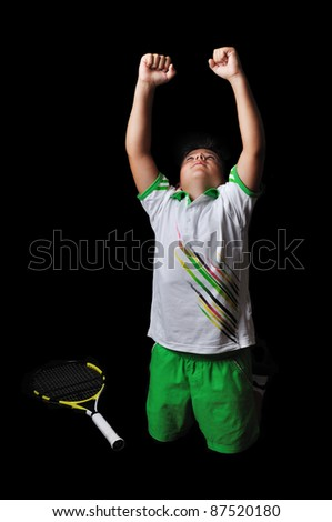 Tennis boy celebrating isolated in black - stock photo