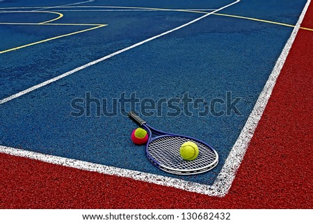 Tennis colored balls and racket, placed in the corner of a synthetic field. - stock photo
