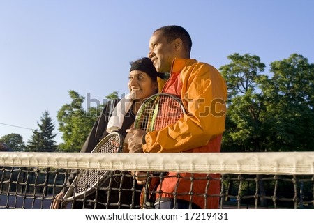 Tennis couple standing at the net holding their rackets and smiling. Horizontally framed photo. - stock photo
