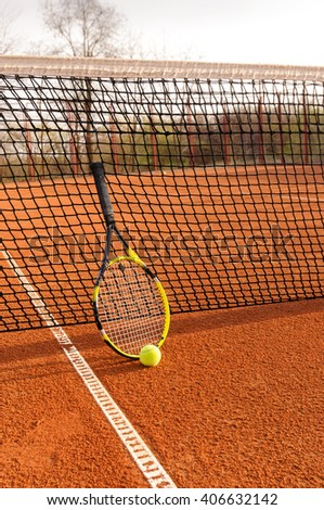Tennis court with a racket and ball on it - stock photo