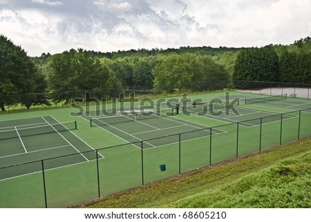 Tennis courts that have been abandoned because of rainy weather. - stock photo