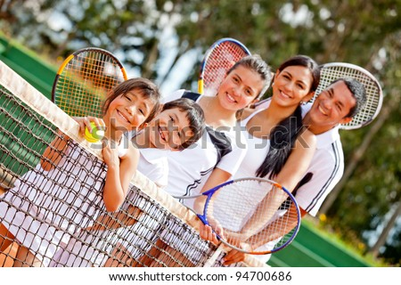 Tennis family standing in a row by the net - stock photo