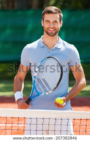 Tennis is my life! Happy young man in polo shirt holding tennis racket and ball while standing on tennis court  - stock photo