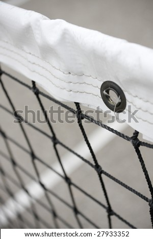 Tennis Net. Close-up of tennis net with white line on court visible in background. Vertical format. - stock photo