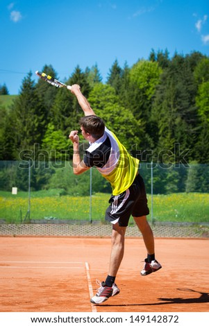 tennis player after hitting the service ball - stock photo