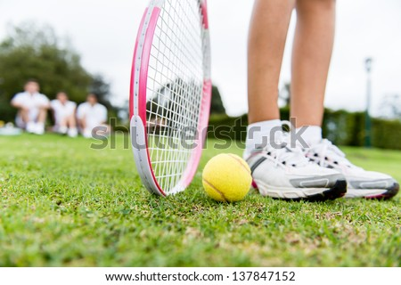 Tennis player at the court with racket and a ball