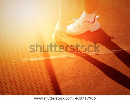 tennis player getting tennis ball from the court - stock photo