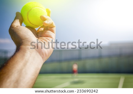 Tennis player holding the ball and getting ready to serve. - stock photo