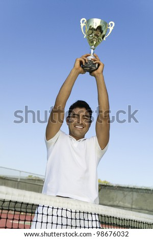 Tennis Player Holding Trophy Over Head