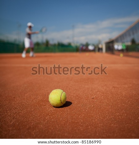 Tennis player in action on tennis court (selective focus, focus on ball in the foreground) - stock photo