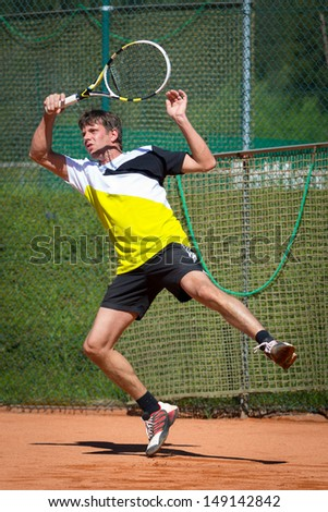 tennis player jumps after playing forehand ball - stock photo