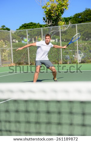 Tennis player - man hitting forehand playing outside on hard court. Male sport fitness athlete practicing in summer outdoors living healthy active lifestyle. - stock photo