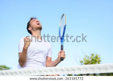 Tennis player man winning cheering celebrating victory. Winner man happy in celebration of success and win. Fit male athlete on tennis court outdoors holding tennis racket in triumph by the net. - stock photo