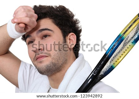 Tennis player wiping the sweat from his brow - stock photo
