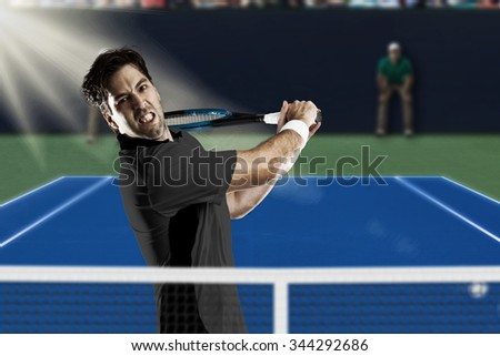 Tennis player with a black shirt, playing on a fast tennis court.