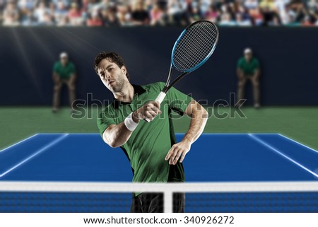 Tennis player with a green shirt, playing on a fast tennis court.
