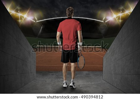 Tennis player with a red shirt, entering a clay tennis court.