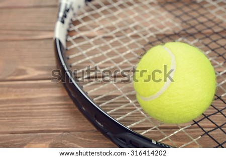 Tennis racket and ball on a brown background, close-up