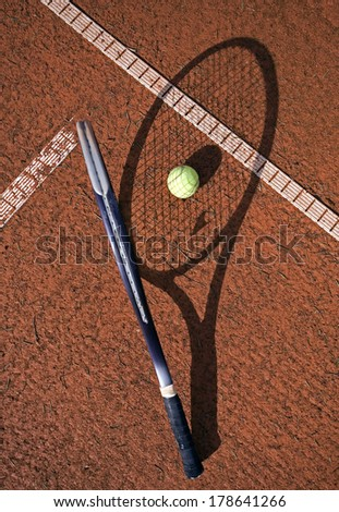 Tennis racket and ball on a clay court - stock photo