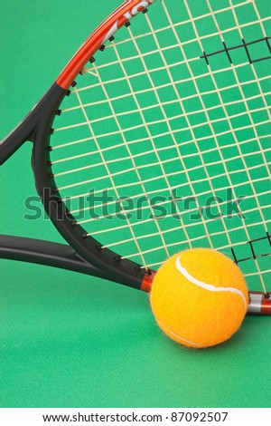 tennis racket and  ball on a green background - stock photo