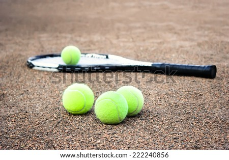 Tennis racket and balls on the clay tennis court - stock photo
