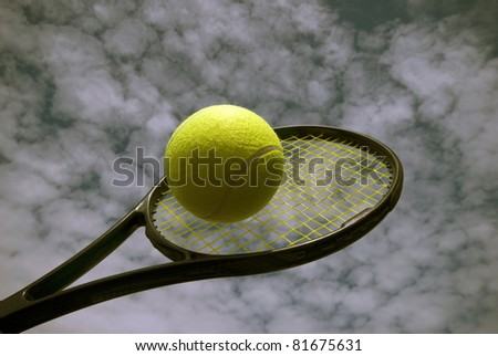 Tennis racket and yellow ball high up and cloudy weather. - stock photo