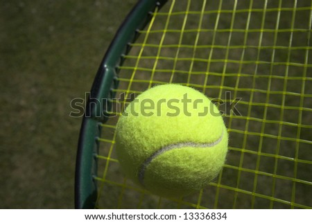 Tennis racket and yellow tennis ball on green grass - stock photo