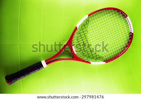 Tennis racket over green synthetic surface, horizontal image
