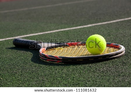 tennis racket with a ball on court - stock photo