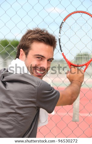 tennisplayer all smiles holding racket near court - stock photo