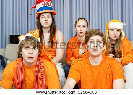 Tense faces of sports fans, watching a game at home - stock photo