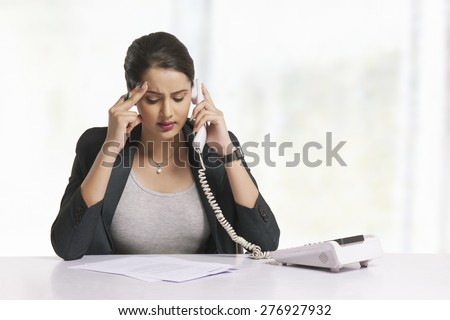 Tensed businesswoman answering telephone at office desk - stock photo