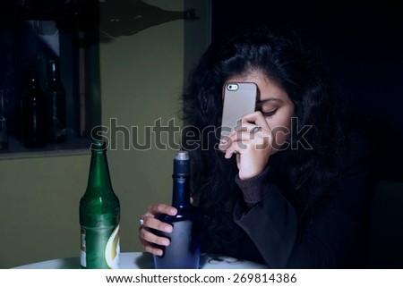 Tensed Indian woman boozing after business loss. - stock photo