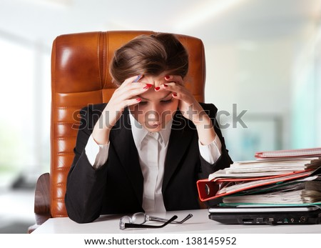 Tensed young business woman holding her head while at work - stock photo