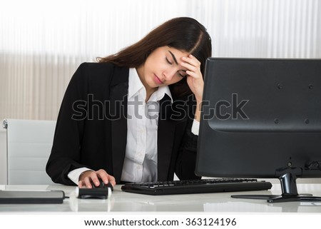 Tensed young businesswoman sitting with head in hand at computer desk in office