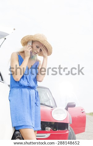 Tensed young woman using cell phone by broken down cars - stock photo